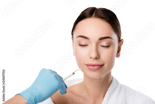 Leinwanddruck Bild doctor in latex glove giving lip injection with syringe to beautiful woman isolated on white