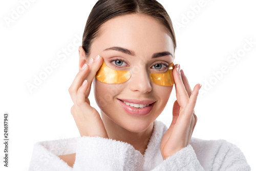 Leinwanddruck Bild beautiful smiling woman with golden eye patches looking at camera isolated on white
