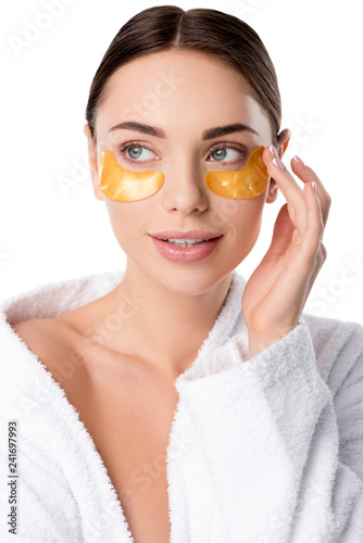 Leinwanddruck Bild beautiful woman in white bathrobe with golden eye patches isolated on white