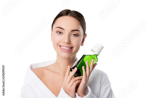 beautiful smiling woman in bathrobe holding mouthwash and looking at camera isolated on white