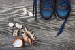 Flat lay photo of sneakers top view, toned image on wooden background with copy space. Seashells. Vacation concept