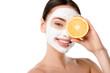 Leinwanddruck Bild - attractive woman with facial skin care mask holding orange in front of face isolated on white