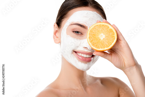 Leinwanddruck Bild attractive woman with facial skin care mask holding orange in front of face isolated on white