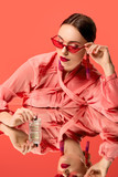 glamorous woman in blouse and red sunglasses posing with perfume bottle and mirror reflection isolated on living coral