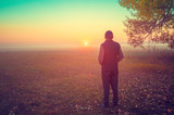 A man stands in the field early in the morning and looks at the sunrise - 241703100