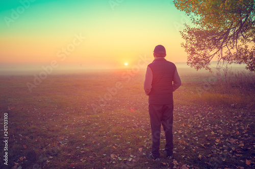 A man stands in the field early in the morning and looks at the sunrise