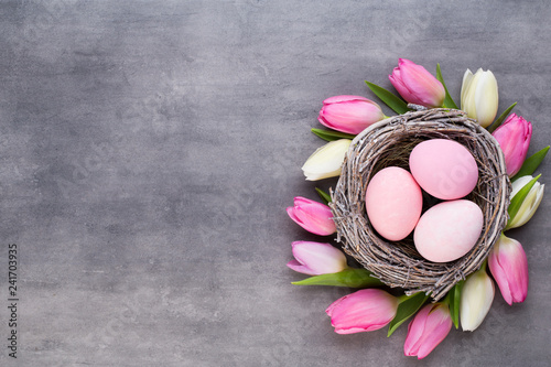 Leinwanddruck Bild Pink tulip with pink eggs nest on a gray background. Easter greetings card.