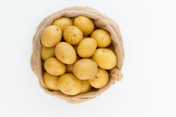 Sack of fresh raw potatoes on wooden background, top view © gitusik