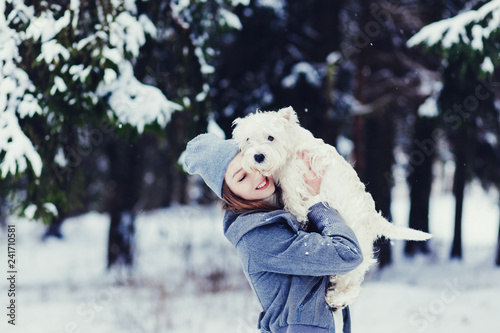 Happy beautiful young woman hugging dog in a winter day