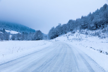 Snowy road during winter through forests and mountains