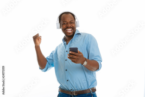Delighted happy man holding his modern smartphone - 241713119