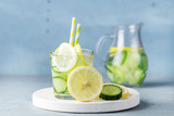 Detox Water with Cucumber and Lemon Summer Drink in Glass Jars on Blue Concrete Background Horizontal