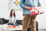 back view of man holding red birthday present behind back with smiling woman on background - 241719597