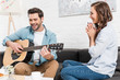 woman sitting on couch and listening man performing with acoustic guitar at home