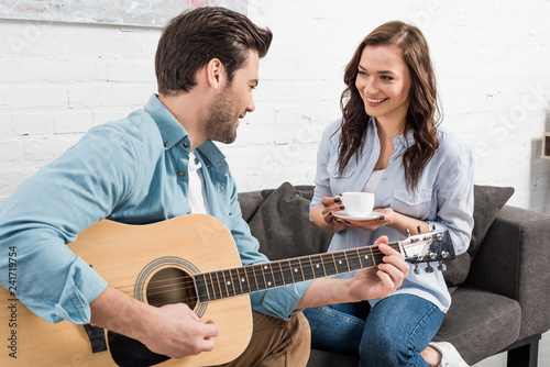 woman sitting on couch and drinking coffee while man playing acoustic guitar at home