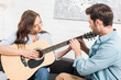 man sitting on couch and teaching woman to play acoustic guitar at home