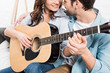 cropped view of couple sitting on couch and playing acoustic guitar at home