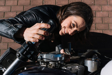 Woman who revises motorcycle in the street