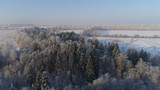 aerial view village among the fields and forests in winter. winter landscape snow covered field and trees in countryside.