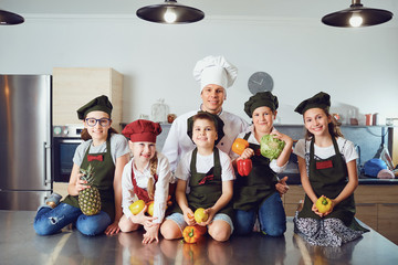 Chef and kids with vegetables in stylish kitchen
