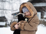 Happy little girl with a newborn lamb in her arms - 241729780