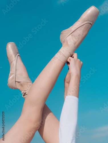 Touching the sky. Pointe shoes worn by ballet dancer. Ballet slippers. Ballerina shoes. Ballerina legs in ballet shoes. Female feet in pointe shoes. Classic dance style. Concert dance performance
