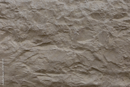 Beige stone surface with deep relief.