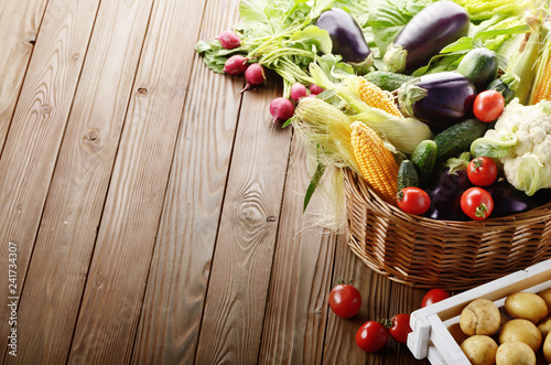 Basket of Organic vegetable food ingredients and crate of potatoes on wood background - 241734307