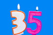 Number thirty five shaped burning candle on blue