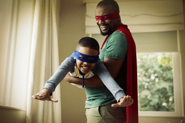 Son and father pretending to be a superhero at home © vectorfusionart
