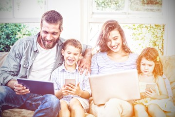 Family using technologies while sitting on sofa © vectorfusionart