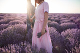 Young girl in the romantic dress and her man in the lavender fields