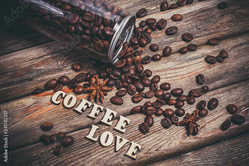 Plastic transparent bottle with coffee beans and the words love coffee on a wooden table and coffee grains nearby