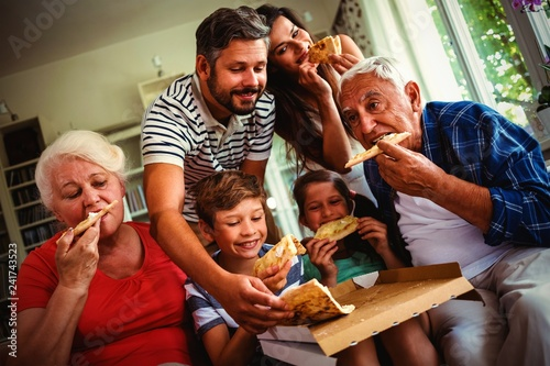 Multi-generation family eating pizza together