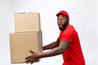 Leinwandbild Motiv Delivery Concept - Side view Portrait of Happy African American delivery man in red cloth holding a box package. Isolated on Grey Background. Copy Space