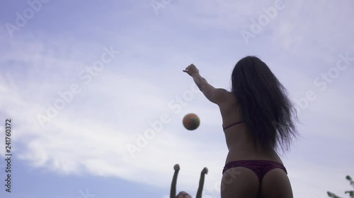 Two hot girls playing volleyball in sexy bikini outdoor on the background of summer blue sky. Rest of two sexy girlfriends in swimsuits. Slow motion.