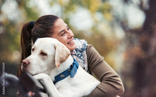 Leinwanddruck Bild Young woman with a dog in the park. Pets and animals concept