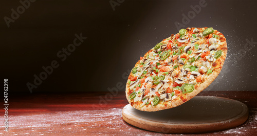 classic pizza on a dark wooden table background and a scattering of flour. pizza restaurant menu concept - 241762398