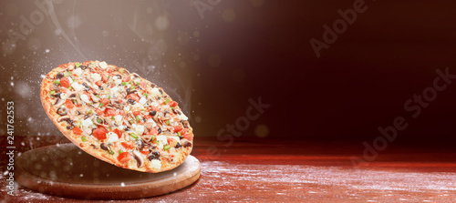classic pizza on a dark wooden table background and a scattering of flour. pizza restaurant menu concept - 241762553