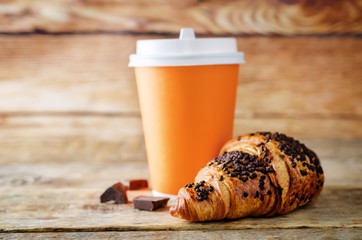 Fresh chocolate croissant with chocolate sprinkles on a wood background