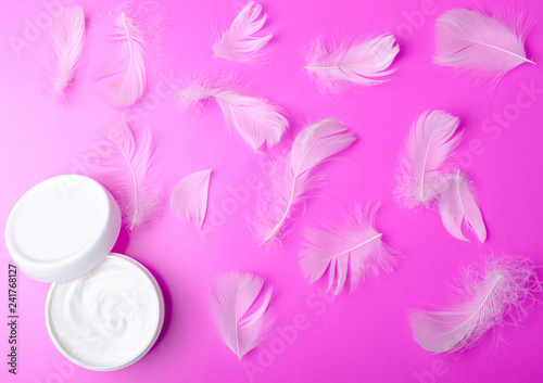 Leinwanddruck Bild White jar cream and feather tenderness beauty on a pink background, top view