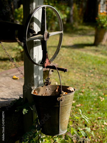 A water well with an old bucket - 241768174