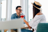 Young happy amorous couple celebrating with red wine at restaurant. - Image - 241772360