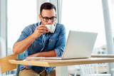 Happy man drinking coffee and looking at his laptop. - Image - 241774360