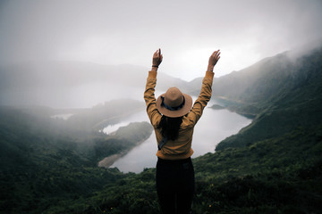 woman traveler holding hat and looking at amazing mountains and forest, wonderful travel concept, space for text, atmospheric epic moment, azores ,portuhal, ponta delgada, sao miguel