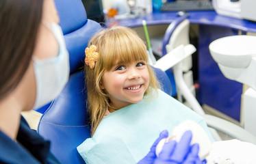 Little girl sitts in the dentist's office