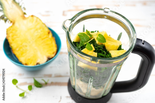 Top view of blender with pineapple and spinach peaces