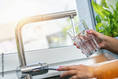 woman holding glass at water tap and filling water