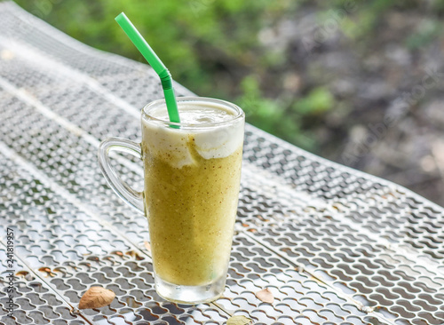 Glass of healthy cold drinks kiwi smoothie with cream on steel grating bar.