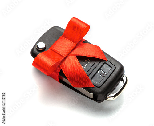 Gift Car keys with remote control alarm with red ribbon with bow. Isolated on white background. - 241821182